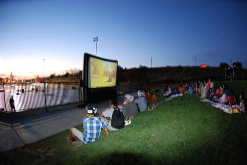 Skateboarders sitting in the grass at a skatepark watching a movie on a large screen