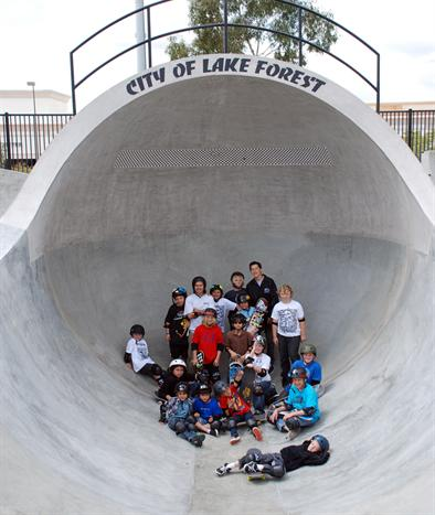 A group of children sitting on a skate structure